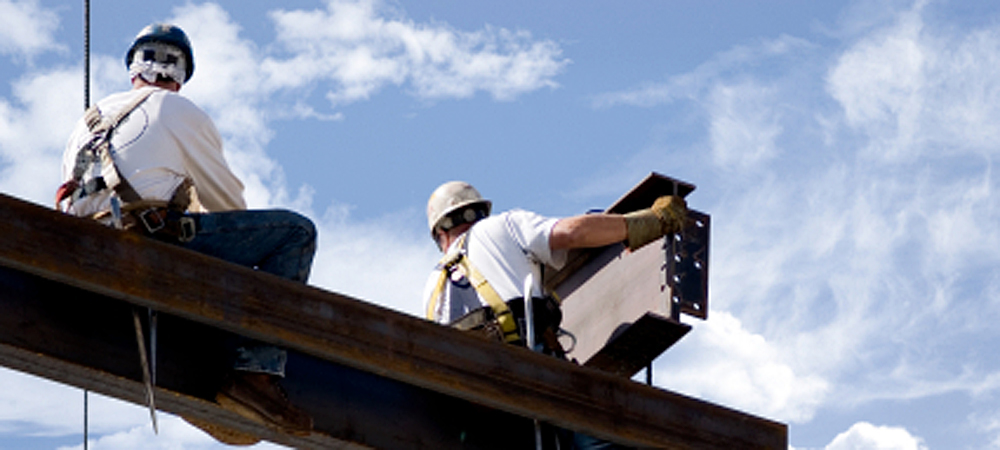 Men in hard hats work on steel beams high in the air.